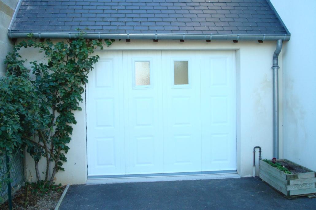 Le client souhaitait remplacer son ancienne porte de garage manuelle en bois par une porte de garage motorisée. Le garage n'avait pas assez de hauteur pour installer une porte de garage plafond ; Nous lui avons donc proposé une porte latérale sur-mesure. 2 hublots sont intégrés pour permettre la luminosité à l'intérieur du garage. Maintenant de sa voiture le client peut ouvrir la porte de garage facilement. #Porte de garage latérale #Porte de garage sectionnelle ou sectionale #Installation par notre propre équipe de pose #Fabrication française par notre partenaire #Blanc #Hublots #Finition par cassettes #Sur-mesure #Motorisation #Dans un pavillon sur Blois (41) #Pour particulier