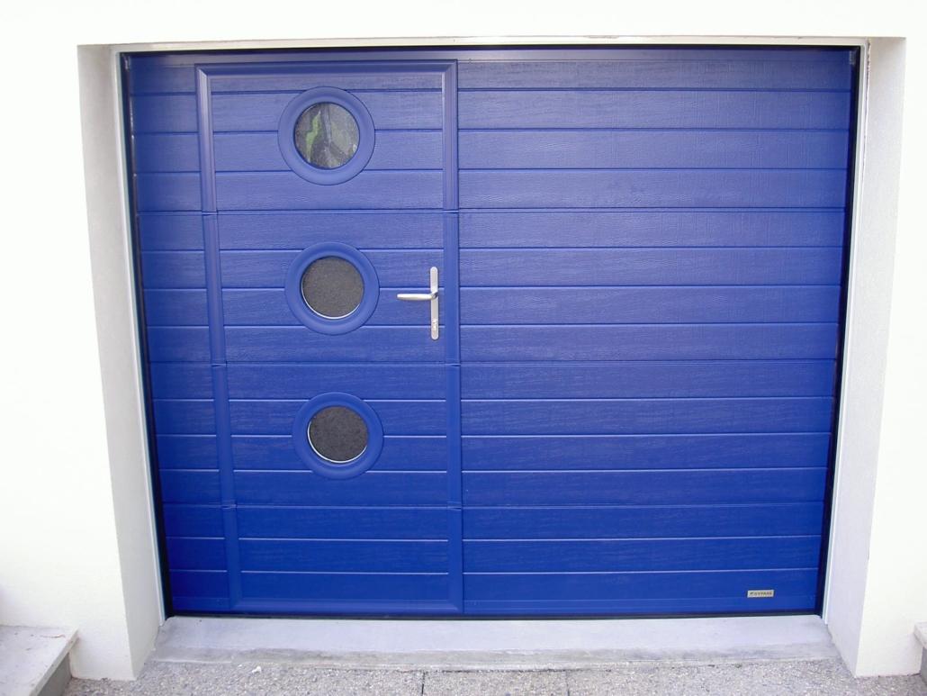 Le client souhaitait remplacer sa porte de garage manuelle par une porte de garage motorisée. Comme le client entre par sa porte de garage pour entrer chez lui, nous lui avons proposé une porte de garage avec portillon. Pour donner plus de design, nous avons intégré des hublots dans le portillon et cela permet d'avoir la luminosité à l'intérieur du garage. Maintenant de sa voiture le client peut ouvrir sa porte de garage facilement. Il peut sortir facilement ses poubelles et de chez lui rapidement par le portillon. #Porte de garage plafond avec portillon intégré #Porte de garage sectionnelle ou sectionale #Installation par notre propre équipe de pose #Fabrication française par notre partenaire #Bleu électrique #Hublots ronds #Sur-mesure #Motorisation #Dans un pavillon sur Château Renault #Pour particulier
